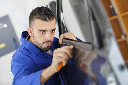 Photo pour Mechanic fitting car door rubber trim - image libre de droit