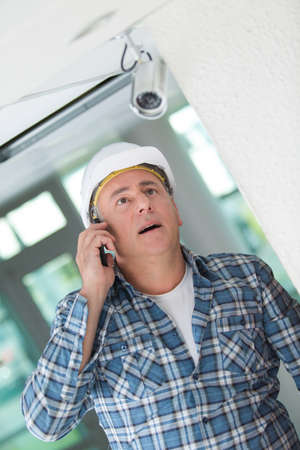 Photo pour Contractor looking at security camera and talking on telephone - image libre de droit