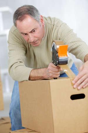 Photo pour Man sealing cardboard box with brown tape - image libre de droit