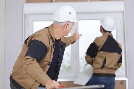 Photo pour Men fitting new pvc window - image libre de droit