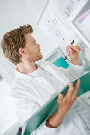 Photo pour Scientist holding folder and writing on whiteboard - image libre de droit