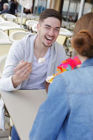 Photo pour Laughing young couple eating in cafe - image libre de droit