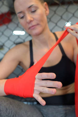 Photo pour woman is wrapping hands with red boxing hand wraps - image libre de droit
