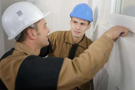 Photo pour Two workmen by pvc window - image libre de droit