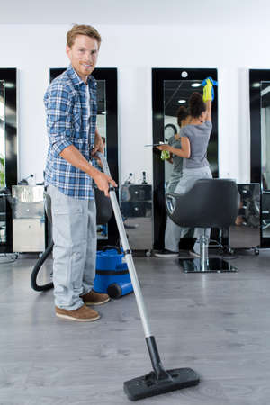 Photo pour Portrait of man vacuuming business premises - image libre de droit