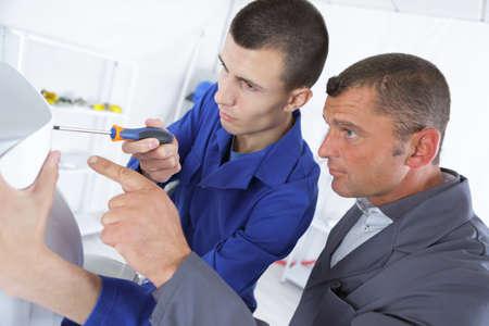 Foto de apprentice fixing something with the help of his teacher - Imagen libre de derechos