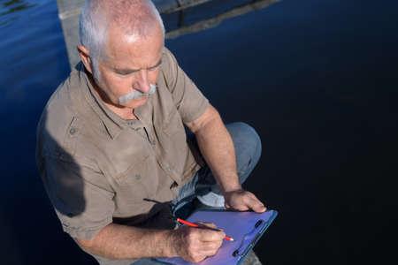 Photo pour worker writing on the clipboard - image libre de droit