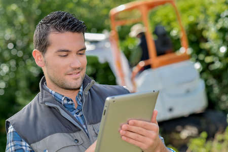 Photo pour Man looking at tablet, digger working in background - image libre de droit