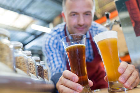 Foto de brewer in uniform tasting beer at the brewery - Imagen libre de derechos