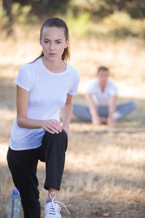 Photo pour young woman stretching before a run outdoors - image libre de droit