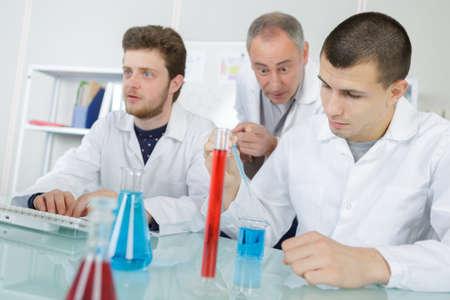 Foto de sscientists going to mix to liquids in lab - Imagen libre de derechos