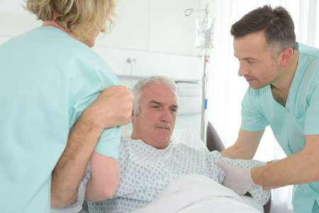 Photo for Medical workers helping patient rise from bed - Royalty Free Image
