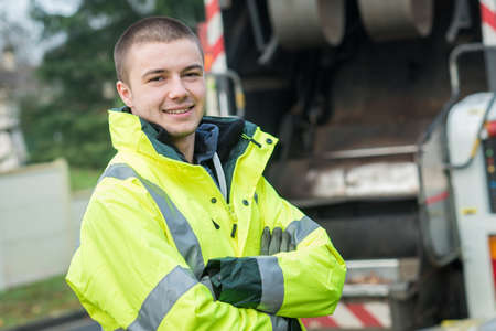 Photo pour young garbage collector standing near his truck - image libre de droit