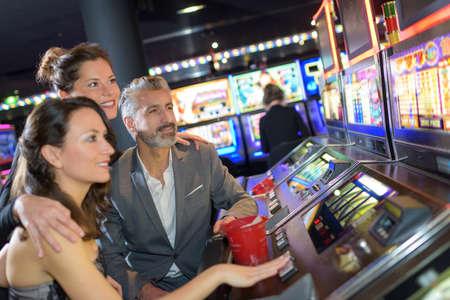 Photo pour friends looking at the slot machine - image libre de droit