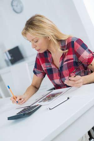 Photo pour A middle aged female working on a desk at home - image libre de droit