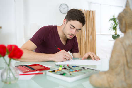 Photo pour A creative young man drawing at home - image libre de droit