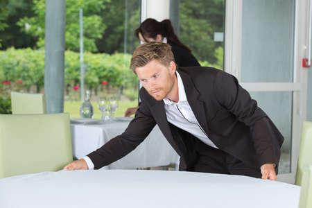 Photo pour A restaurant staff putting table covers - image libre de droit