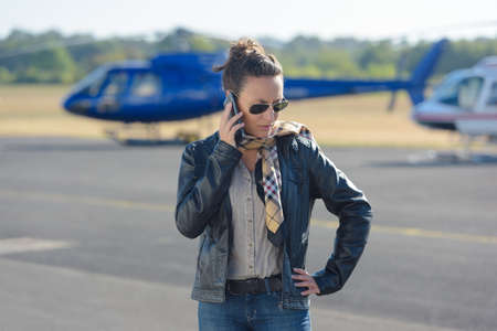 Photo pour Beautiful pilot talking to the phone in front the helicopter as background - image libre de droit