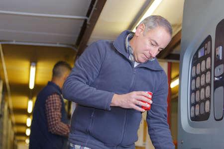 Photo pour Man getting drink from vending machine - image libre de droit