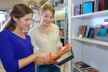 Photo pour women shopping notebooks and writing paper in stationary store - image libre de droit