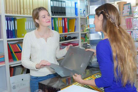 Photo pour Woman looking at folder in stationery shop - image libre de droit