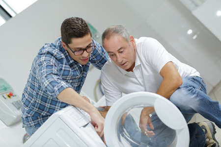 Photo for trainee and mentor fixing a washing machine - Royalty Free Image