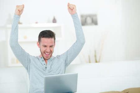 Photo pour Man using laptop making triumphant gesture - image libre de droit