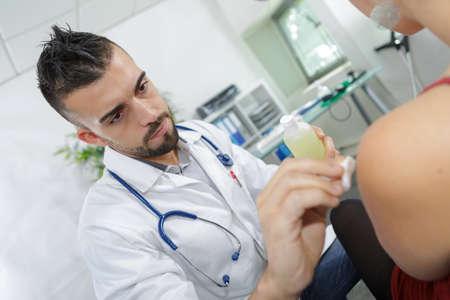 Foto de young male doctor preparing for an injection - Imagen libre de derechos