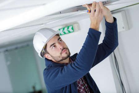 Photo pour male electrician with screwdriver repairing fire sensor - image libre de droit
