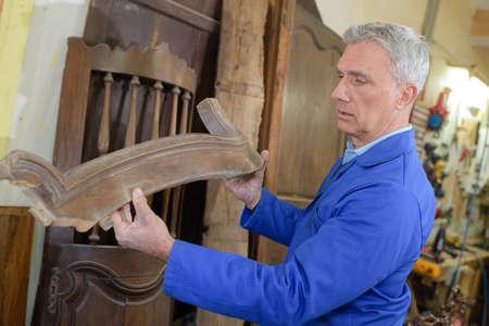 Photo pour senior worker fixing furnitures in his workshop - image libre de droit