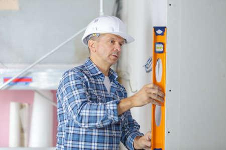 Photo pour professional builder with spirit level at construction site - image libre de droit