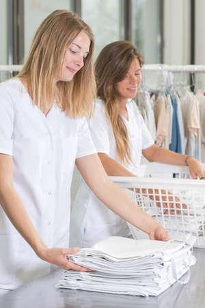 Photo pour smiling female workers in laundry service - image libre de droit