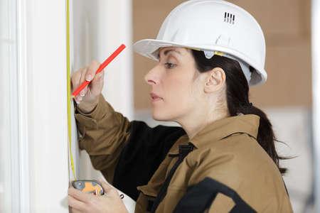 Photo pour low angle shot of female carpenter working with spirit level - image libre de droit