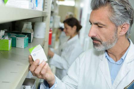 Photo pour pharmacist checking medication in pharmacy - image libre de droit