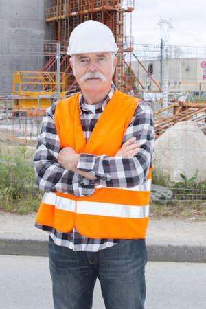 Photo pour happy senior construction worker smiling with arms crossed - image libre de droit
