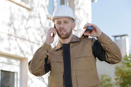 Photo pour portrait of contractor outdoors using telephone spirit level on shoulder - image libre de droit