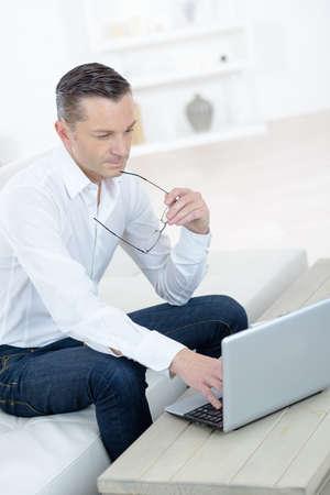 Photo pour man work for laptop on sofa - image libre de droit