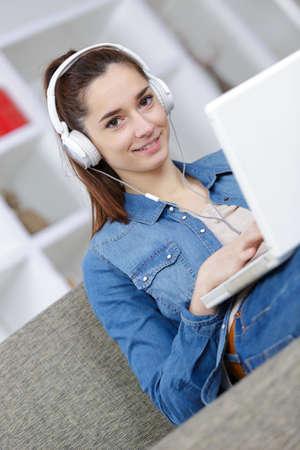 Photo pour brunette with headphones on the sofa - image libre de droit