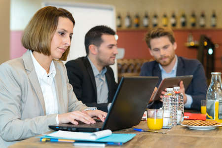 Photo pour team of business people working in cafe with laptops - image libre de droit