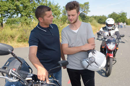 Photo for Man explaining motorcycle controls to young man - Royalty Free Image