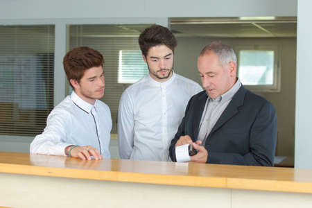 Photo pour apprentices receptionist at the counter with instructor - image libre de droit
