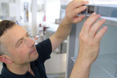 Photo pour Man touching temperature display on refrigerator - image libre de droit