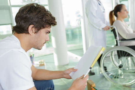 Photo pour young man reading while waiting in the hospital lobb - image libre de droit