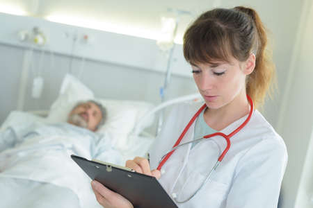 Photo pour physiotherapist writing on clipboard in clinic - image libre de droit