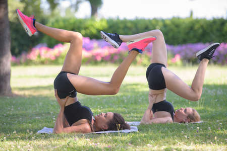 Photo pour two concentrated young spotswomen stretching legs outdoors - image libre de droit