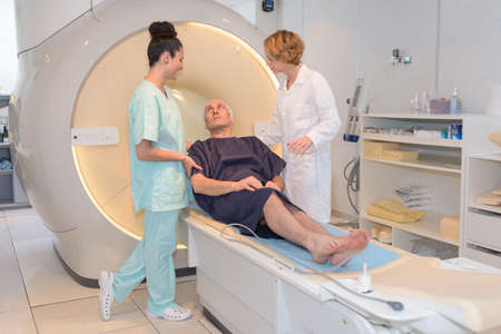 Photo pour nursing staff talking to patient at ct-scanner - image libre de droit