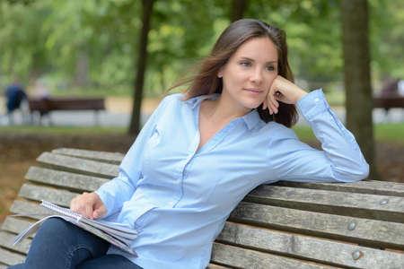 Photo pour female writer sitting on the park bench - image libre de droit