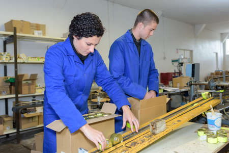 Photo pour young workers packing products off of factory production line - image libre de droit