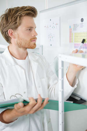 Photo pour man in lab-coat holding folder looking at plans on wall - image libre de droit