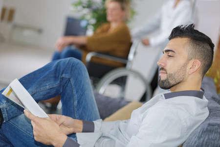 Foto de young man waiting for the doctor in hospital lobby - Imagen libre de derechos